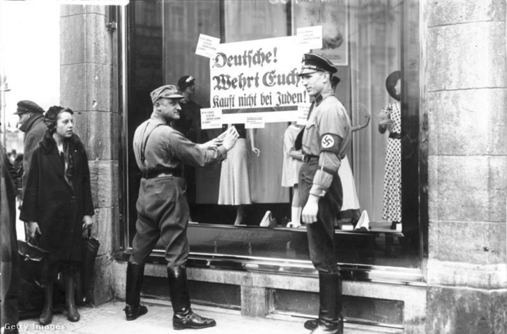 Bojkottra felszólító plakátot ragaszt ki egy katona egy zsidó kereskedő üzletének kirakatára Berlinben (1933.)