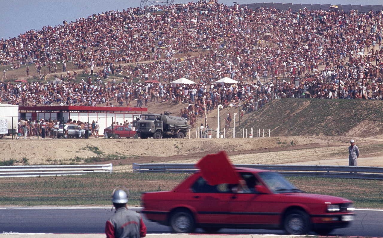 Ime a biztonsági kocsi, azaz a Safety Car, itt épp zárja a pályát a piros zászlóval. Akkoriban még BMW volt, ma már Mercedes. A háttérben a 200 ezres közönség egy része. Csak a versenynapon voltak ennyien, ez megdönthetetlen örökrekordnak tűnik.