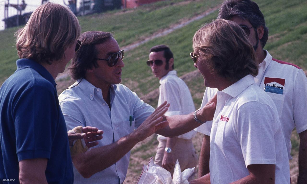 A háromszoros világbajnok Jackie Stewart az egyszeres világbajnok Keke Rosbergnek magyaráz. A finn - Nico Rosberg apja - McLarennel indult az I. Magyar Nagydíjon. Ötödiknek kvalifikált, de a 34. körben autóhiba miatt kiállt. Stewart még ma is magyaráz, gyakran feltűnik versenyeken, Rosberg viszont csak a tavalyi abu-dzabi futamra ment el, ahol a fia megnyerte a világbajnokságot.