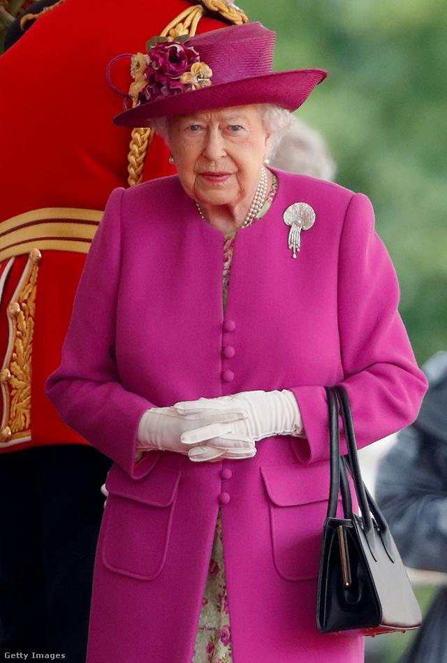 Magenta rózsaszín kabát és kalap fehér kesztyűvel a londoni Horse Guards Parádén.