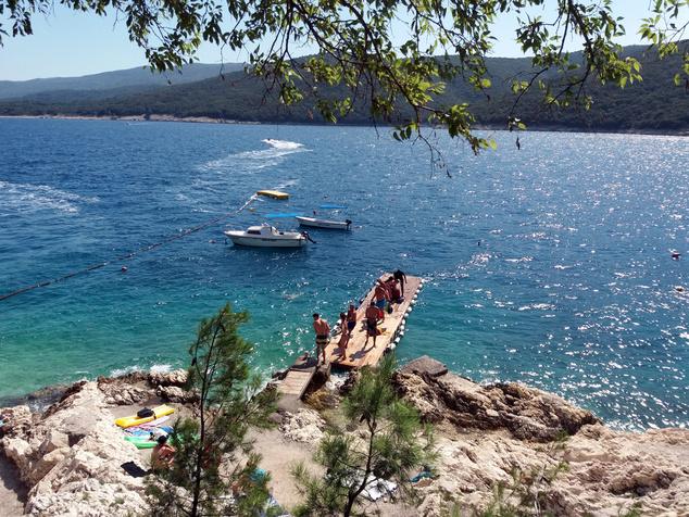 A képeslapra illően szép öbölből a Cres, a Losinj és a Krk szigetekre is rálátni (A fotó közepén lévő mobil stéggel juttatják a turistákat a parttól távolabb lehorgonyzó kishajókhoz. Ha pedig visszatértek a hajókázásról, a stéggel együtt egy kötéllel húzzák vissza őket a partra.)