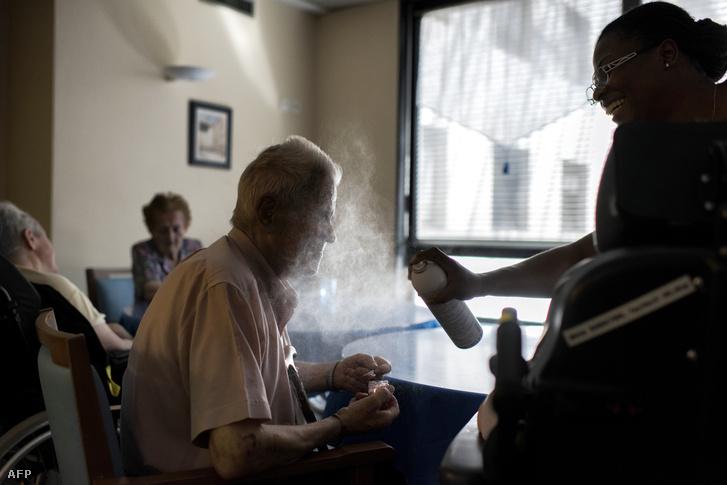 Nővér fúj vízpermetet egy idős férfi arcára a hőségben egy lyoni öregek otthonában, Franciaországban 2017. augusztus 5-én