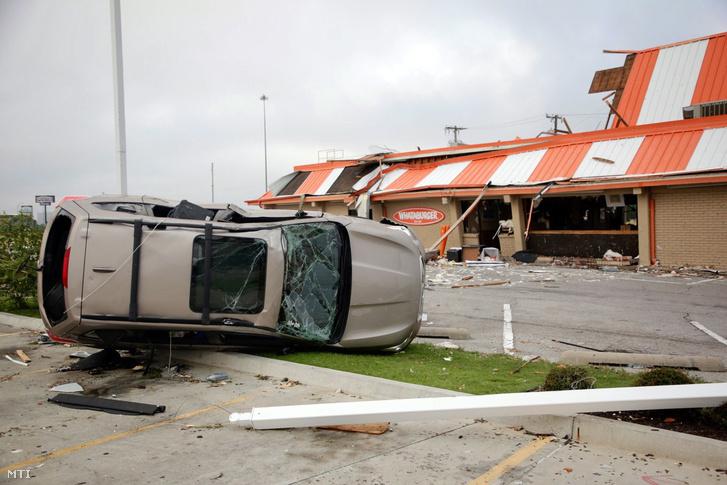 Oldalára fordított jármű egy megrongálódott gyorsétterem előtt