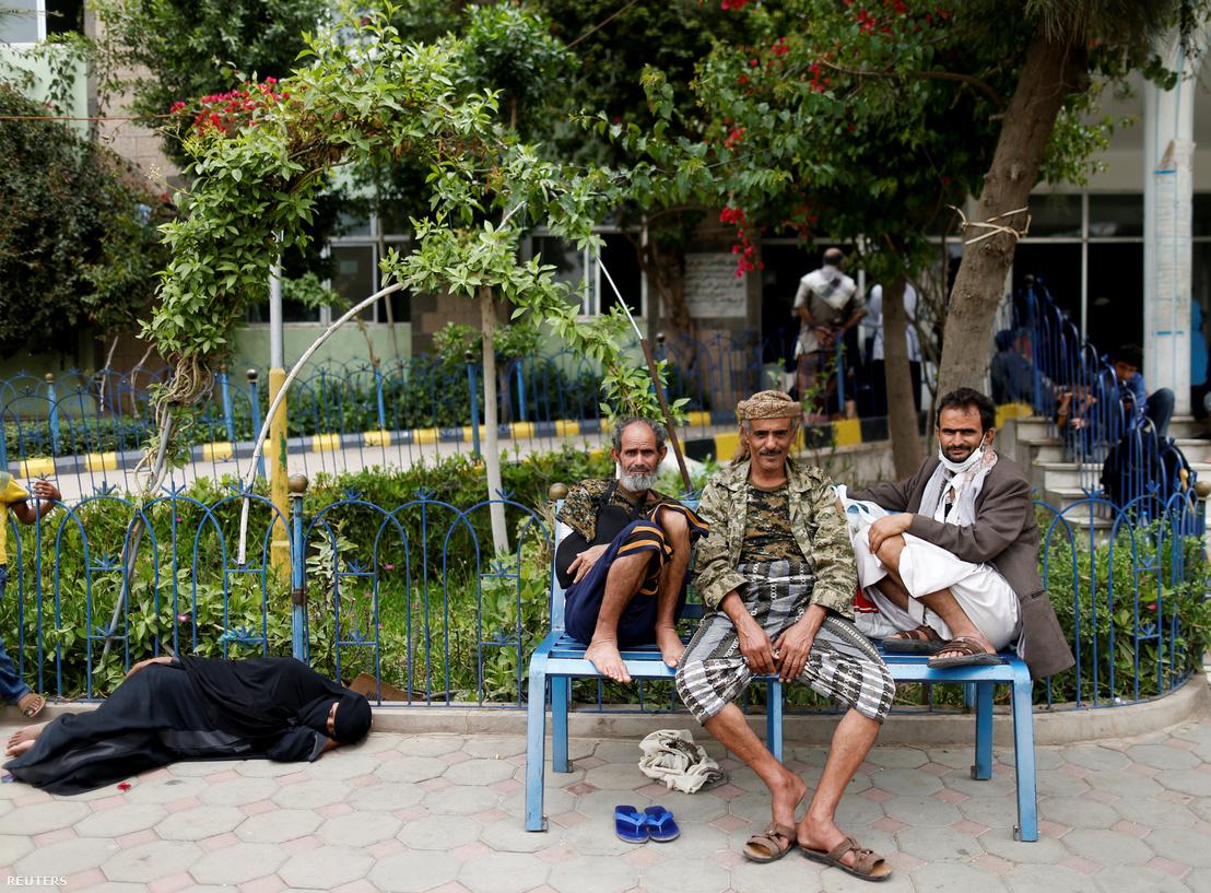 Férfiak ülnek a padon, egy nő pedig a földön fekszik egy kolerás beteg számára fenntartott intézmény udvarán, Szanaában.