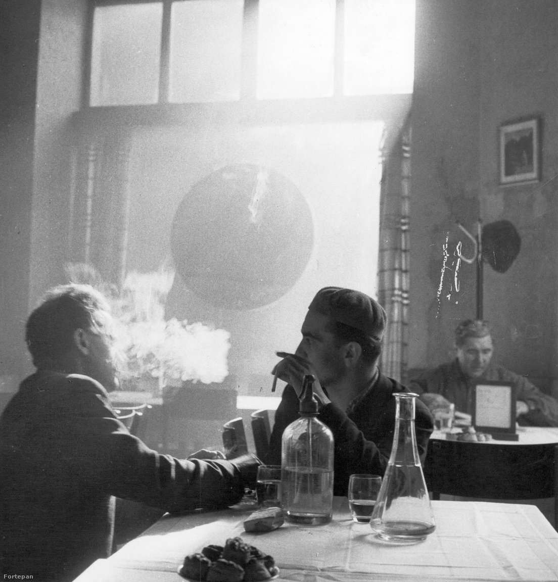 Kiss Imre, szódaszónok: Egy kisvendéglő a Ferencvárosban, 1965Korai eszmélésem egyik hangulati összefoglalása ez a kép. Arra csak a közelmúltban döbbentem rá, hogy a szóda milyen fontos – volt és lesz – az életemben, de a gomolygó füst és az odafordulás a fehér abrosz felett már gyerek fejjel is a társas lét egyik tipikus életképe volt számomra. Hogy fröccsöztek az is nyilvánvaló, az üres karaf árulkodik és árválkodik, várva az újratöltést.                          A pogácsa már csak a ráadás.