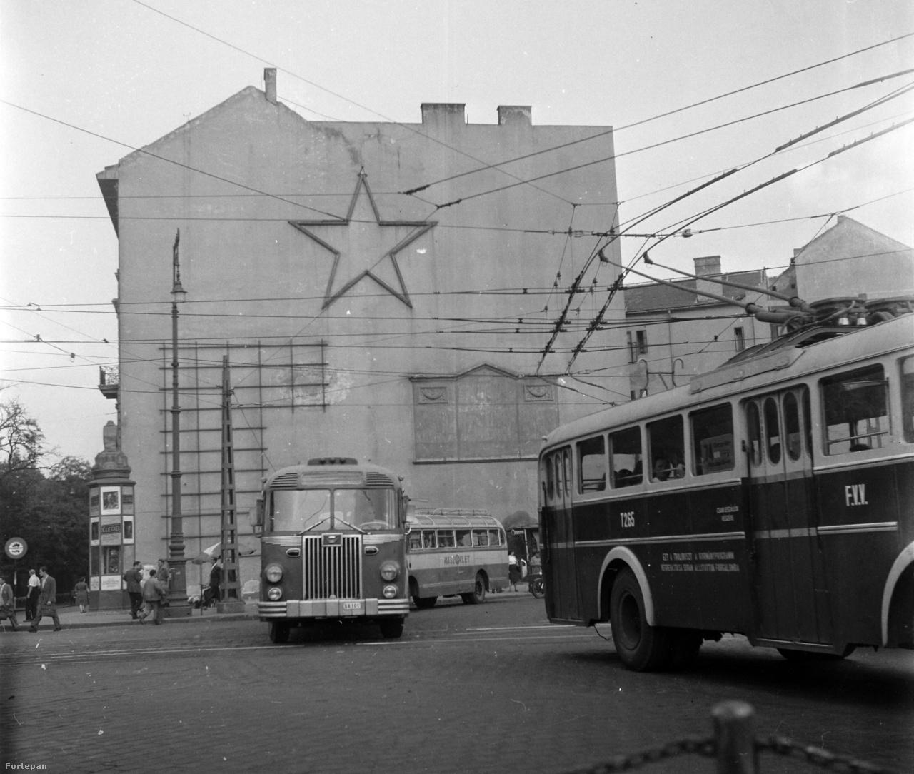 """Hetényi Zsuzsa egyetemi tanár, műfordító: ÉletjelA Fortepan remek böngészési módja egy év átlapozása.1954: még golyónyomok, hiányzó tetők és hidak, szürkeség és rend, sok foghíjtelek.Ezen a Kálvin térin a Magyar-Holland Biztosítótársaságnak az ostrom végén eltűnt épületében a később eltűnt Raoul Wallenberg irodája működött száznál több emberrel.A kép csupa rejtvény.Az üres falon emeletnyi magasan kő triptichon, talán díszterem-maradvány.Baloldalt magasra kúszó lécrács – minek?                         Közöttük, de nem középen vas vörös csillag uralkodik.A mából úgy látom, hogy a troli vezetékei érvénytelenítik.A régi járműcsoda rendszámán múltba veszett utópia: X-ben GA úr a 101-es számot kapta.                         Hátul igazi reptéri busz, a Magyar–Szovjet Polgári Légiforgalmi Részvénytársaságé.""""Ezt a trolit …. állította forgalomba"""" – kicsoda?A Múzeum utcába lovas szekérrel behajtani tilos.                         A hirdetőoszlopon filmreklám."""