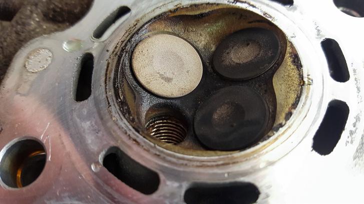 A kipufogószelep teljesen tiszta, arról leégett a koksz, a szívószelepeket viszont nehéz volt kiszedni: annyira kompakt a hengerfej, a két szelep között pedig annyira kevés hely, és olyan kicsik a szelepek, hogy a gyári rugóösszefeszítő célszerszámnak az adaptere alig fért oda – Zsombor cégül esztergált hozzá egy speckó célszerszámot. A szelepek annyira jó állapotban voltak, hogy még egy tisztító becsiszolásra sem volt szükség. A szelepülék körül is minden teljesen tiszta volt, ami nyomokat találtak, azok az üzemszerű működés nyomai voltak