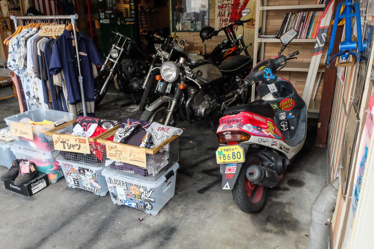 A helyhiány egészen vicces megoldásokra sarkallja a japánokat. Ez itt például egy vagány divatholmikat és rocker-relikviákat árusító, városszéli divatbolt. A tulaja egy harmincas, szőkített japán csávó, megkérdeztem, tőle, mit keresnek itt a motorok. Ja, mondta, a Harley az enyém, a két öreg japán gép a haverjaimé, akikkel motorozunk, a robogó a bolt futármotorja. Díszletnek pont jók ide, s így sikerült megoldtani a garázskérdést is
