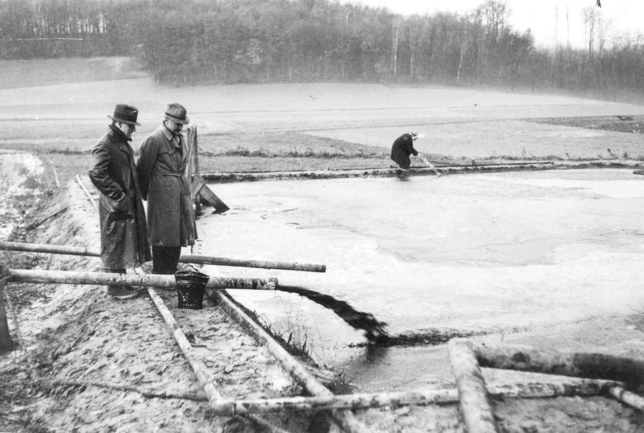 A Budafapuszta-2 (B-2) számú kútból kifolyó kőolaj mellett áll Paul Ruedemann és William Conway 1937. november 21-én. Hivatalosan ezzel kezdődött a kőolajtermelés Magyarországon. A B-2 kút a MOL Nyrt. működési területén van.