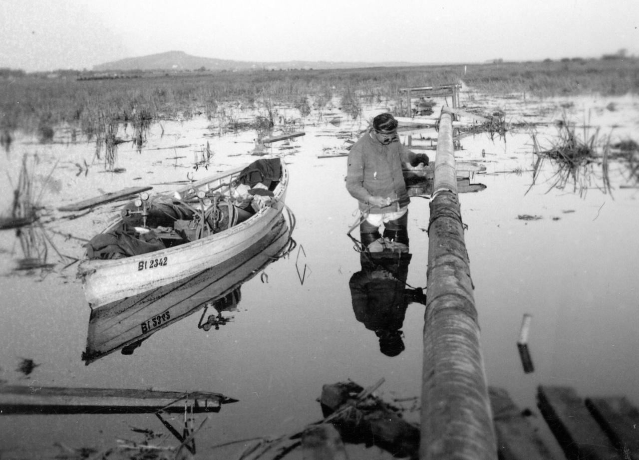 """A zalai 8 colos kőolajvezeték építése: csőhegesztés a Kis-Balatonban. Az egyedülálló """"dugós szállítási"""" technológiának köszönhetően 1949. május 1-jén Bázakerettye és Budapest között egy 8 colos vezetéken megindulhatott a földgázszállítás."""