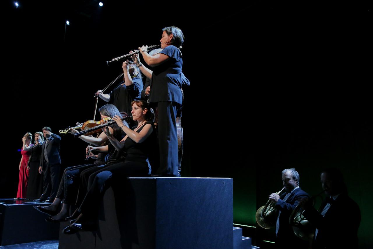 És a játszó színészek a színpadon. Egy nagyon pici lépcső tetejére kellett hangszerekkel együtt felfutniuk, játszaniuk, aztán gyorsan eltűnniük a színpadról.