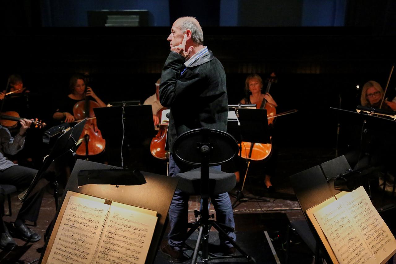 Fischer Iván a másodkarmestert hallgatja. Az üres nézőtér közepén ott ült egy munkatárs, hallgatta próba közben a zenekart, és kommentálta, hogy melyik hangszer hangosabb vagy halkabb a többihez képest.