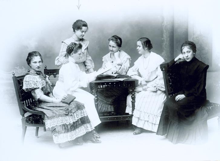 Az olvasás a művelt ifjú hölgyek elfoglaltsága, vagyis mostanra elvetették azt az elképzelést, hogy a nők ne tanuljanak meg írni és olvasni. Széles fodros gallérok, hosszú szoknyák, furfangos hajfonatok. Lányok irodalmi köre Besztercebányán 1904-ben.