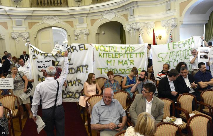 A római-parti mobilgát építését ellenzõ (b) és támogató aktivisták transzparensekkel a Fõvárosi Közgyûlés ülésén a Városháza dísztermében 2017. június 14-én.