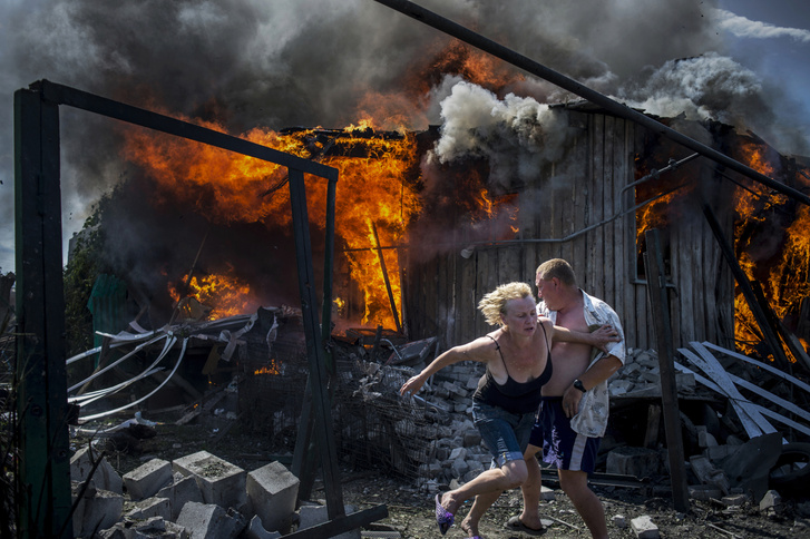 Egy légitámadás miatt lángra lobbanó házból menekülnek a lakók. 2014 áprilisában oroszbarát szeparatisták elfoglalták Donyeck és Luhanszk városok egyes részeit Ukrajna keleti határánál. Az ukrán kormány katonai válaszlépéssel reagált, és a konfliktus háborús helyzetté terebélyesedett. (Hosszú távú munkák -1. díj)