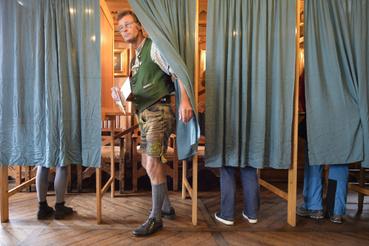 Bajor népviseletbe öltözött férfi lép ki a szavazófülkébõl Schlierseében.