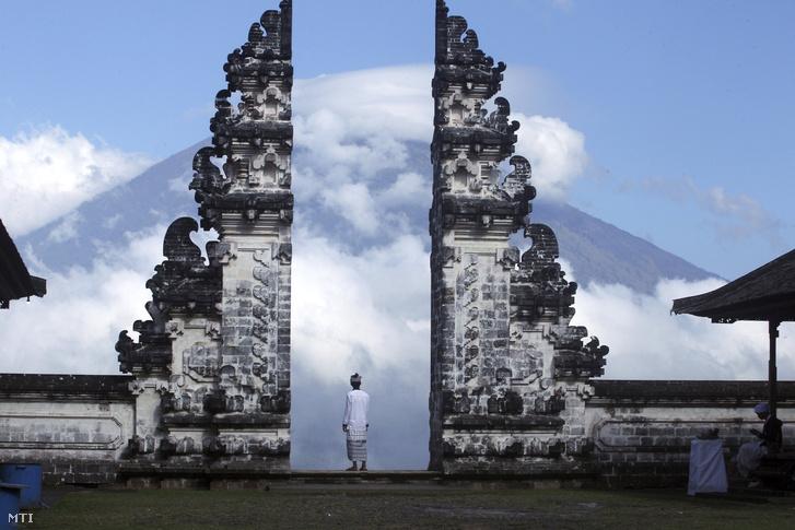 A felhőkbe burkolózott Agung tűzhányót nézi egy indonéz férfi egy templomkerítés kőcsipkéi közt a Bali-szigeti Karangasemben 2017. szeptember 26-án