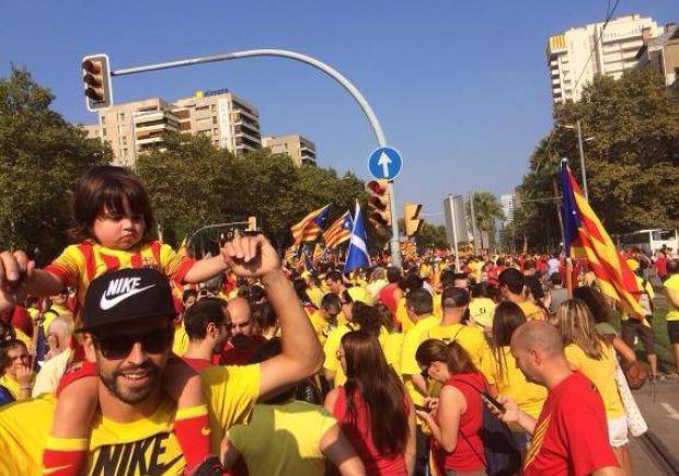 Piqué itt épp a fiával tüntet a függetlenségi szavazásért a Katalónia függetlenségét jelképező piros-sárga sávos katalán nemzeti színekben