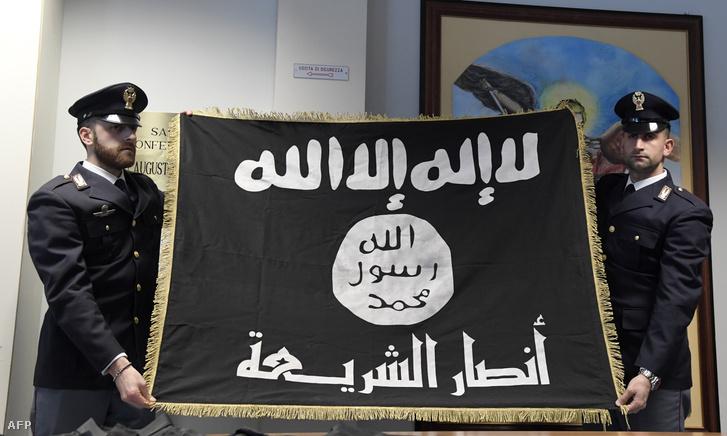 """Olasz rendőrök mutatják be az Iszlám Állam elkobzott zászlóját egy sajtótájékoztatón ahol a """"Black Flag"""" elnevezésű antiterrorista műveletről és egy Hmidi Saber nevű, feltehetően a líbiai Ansar al-Sharia, az al-Kaida terrorhálózathoz köthető csoport tagjának letartóztatásáról számoltak be 2017. január 10-én."""