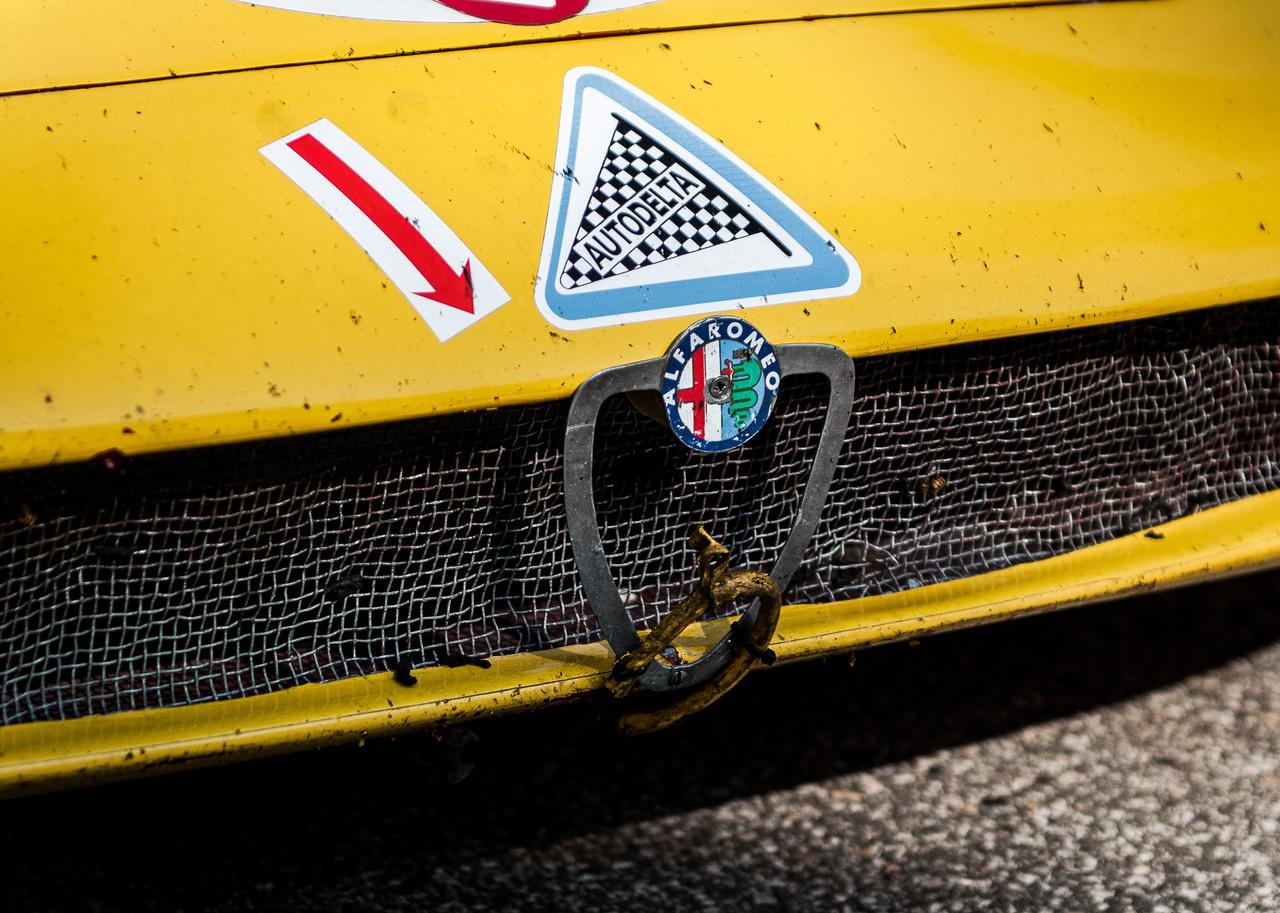 Nehezen lehetne filigránabb: a díszrács körvonala az embléma sziluettjével együtt egy fémlemezből kivágott valami a T33/3 orrán, amit egy igényes csavar tart Alfa-emblémástul a helyén. Hiába, a versenysport nem divatbemutató. Persze ettől még rettentően adja!
