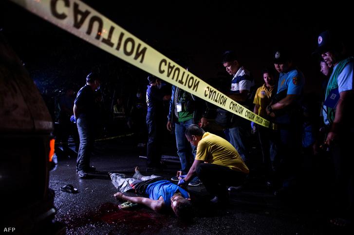Rendőrök helyszínelnek egy kábítószer ellenes akcióban lelőtt férfi holtteste mellett Manilában 2017. május 18-án