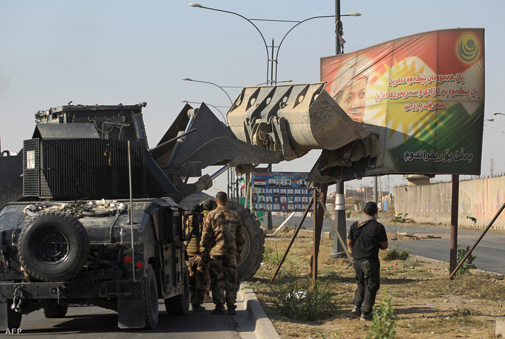 Az iraki hadsereg katonái próbálnak ledönteni egy, a kurd autonóm területek elnökét, Maszud Barzanit ábrázoló táblát Kirkuk közelében 2017. október 16-án