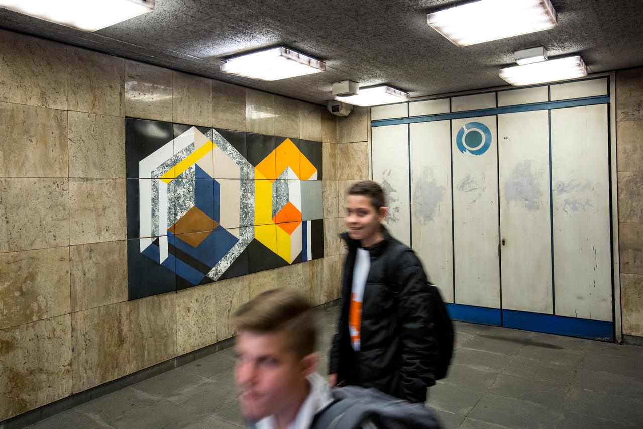 A 2003-ban elhunyt Gulyás Dénes festményei ma is rendszeresen bukkannak fel aukciós házak árverésein. Hogy ide a Forgách utcai metrómegállóba miért pont egy Veszélyben című alkotása került, abba bele se merek gondolni. A másik címe – Hatszemközt – viszont rímel a fenti Madarassy-domborműre. Milyen kár, hogy az nem marad a helyén.
