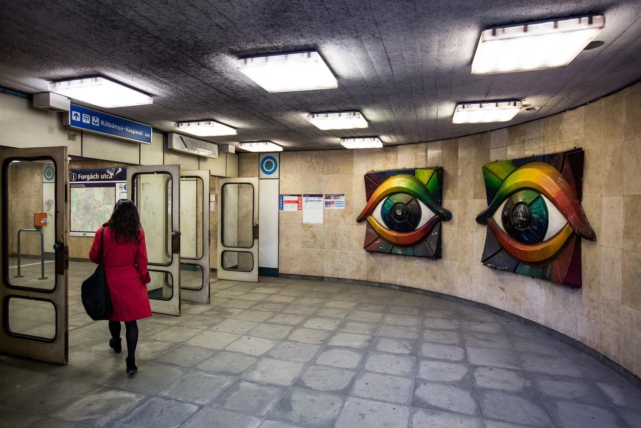 A Fürkésző szemek (Kétszemközt) eléggé elüt a legtöbb metrós műalkotástól, ugyanis nem tűzzománcról van szó, hanem műanyag domborműről. Ifj. Madarassy Walter Forgách utcai szobra ugyan állja a sarat, de eléggé össze van már karcolva. Hogy a restaurálás után hova kerül, épp nem tudni, mint a művész Városkapunál látható Puzzle-jéről sem. Bár a mellette látható körök nem a kompozíció részei, nem árt megjegyezni: az 1990-ben átadott új metrószakaszon nem csak a műalkotások, de a tájékoztató táblák is Nemcsics Antal koloroid rendszerhez igazodtak. Állítólag a Nemzetközi Színtudományi Akadémia színtervező szakos hallgatóinak minden évben tanulmányi kiránduláson mutatták be az új metrószakasz színinformációs rendszerét és a képeket.