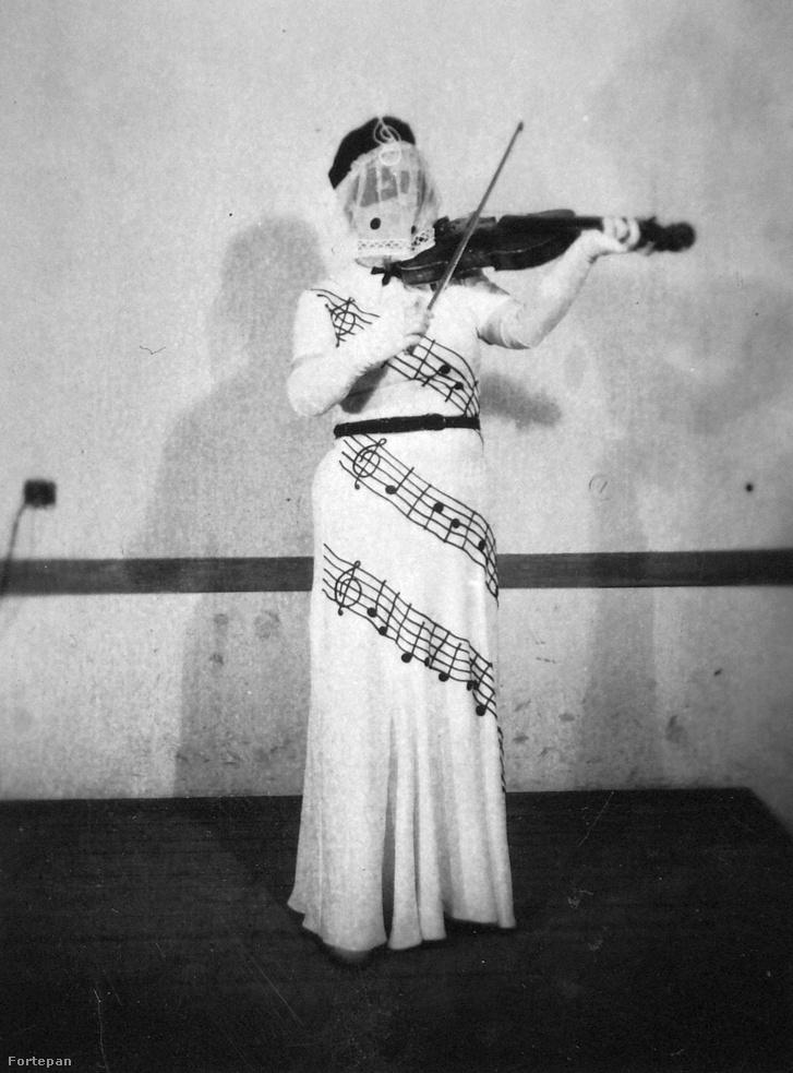 Teljesen értetlenül állunk a jelenség előtt. A nagyon titokzatos hegedűs hölgy egy maszkot és egy fátylat is visel, nehogy fény derüljön a kilétére. Sajnos a jelmez jelentése sem derült ki. (1943)