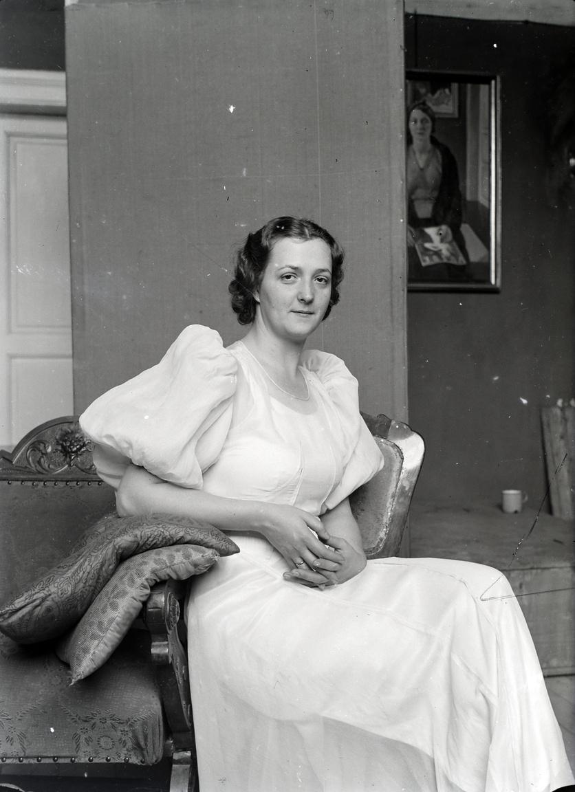 A modellt ülő kisasszonynál is érdekesebb a háttérben lógó festmény: a Női arckép Vogue divatlappal. Ugyanezt a portrét Bánovszkyn kívül Heintz Henrik és Pándy Lajos is megfestett 1932-ben. Bánovszky festménye egy másik fotóról korábbról már ismert, holléte ismeretlen. Pándy és Heintz alkotásait az Magyar Nemzeti Galéria őrzi. Érdekes adalék: a visszaemlékezésben szerepel, hogy az eltűnt képet Bánovszky a nyolcvanas években újrafestette, bár sosem fejezte be.