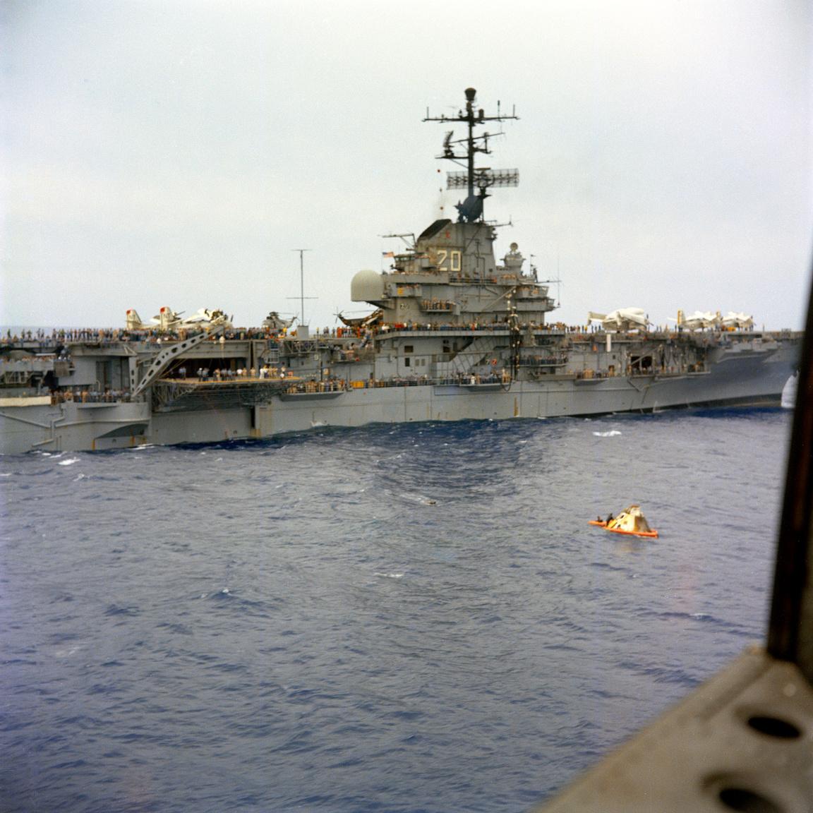 A USS Bennington repülőgéphordozó megközelíti az űrből visszatért parancsnoki modult. Az űrhajónál könnyűbúvárok dolgoznak, hogy felkészítsék a szerkezetet a daruzásra.