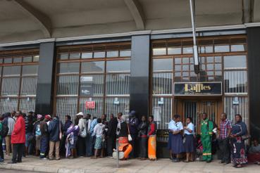 Pénzfelvétel miatt várakozó emberek sorakoznak egy bank elõtt Hararében.