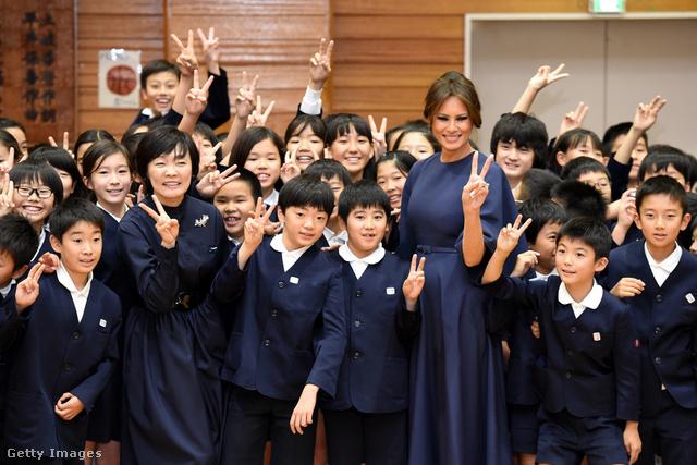 Ebben a vékony övvel átfogott sötétkék Dior ruhában látogatott meg egy tokiói általános iskolát. Az iskolaköpeny színéhez passzoló francia dizájner ruha 2657 fontba, kb.937 ezer forintba kerül a Diornál.