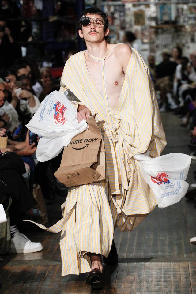 Szatyrokkal rohangáló modell a Vaquera kifutóján New Yorkban.