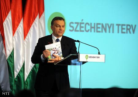 Orbán Viktor az ÚSZT pályázati kézikönyvével (Fotó: Kovács Attila)