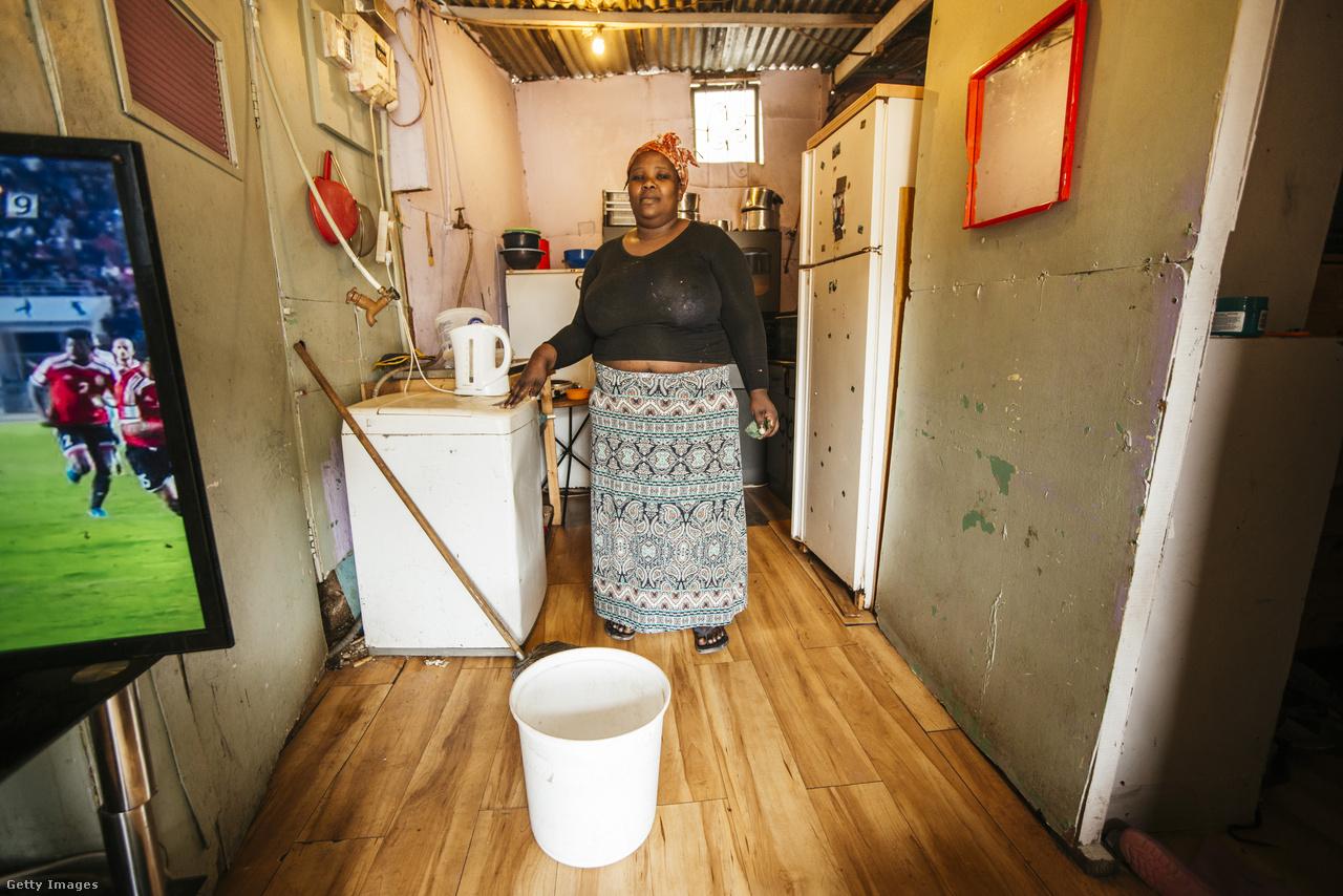 Patricia Gxothelwa mutatja a majdnem üres vödröt, amivel a lakásában kénytelen felmosni a vízkorlátozások miatt.