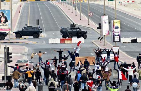 Kormányellenes tüntetők széttárják karjukat a katonai járművek láttan