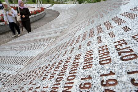 Boszniai muszlim nők sétálnak a szrebrenicai áldozatok emlékére létrehozott emlékmű mellett, Szrebrenica közelében