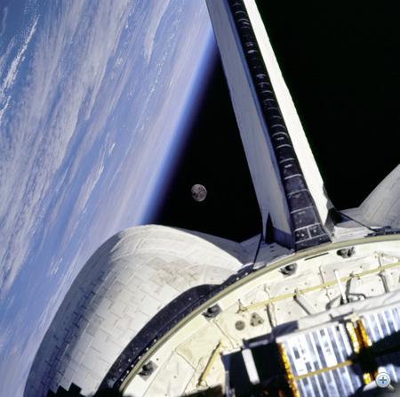 1998. november. Az STS-95-ös küldetésen - 25 repülésén - lévő Discovery, az Atlanti-óceán és a Hold. A fedélzeten ott van a NASA veterán űrhajóshőse, John h. Glenn is, akinek ez a második űrrepülése, miután 1962-ben a Friendship 7-tel első amerikaiként megkerülte a Földet. Glenn ezzel a repüléssel a legidősebb aktív űrhajós címet érdemelte ki.