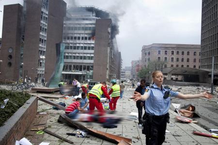 A robbanás után segédkező rendőr (forrás: twitpic.com)