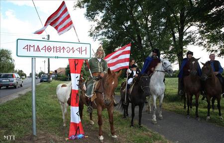 Helybeli lovas hagyományőrzők állnak Rákóczifalva nevét hirdető, székely-magyar rovásírásos helységnévtábla mellett a 442-es számú főút kerékpárútján