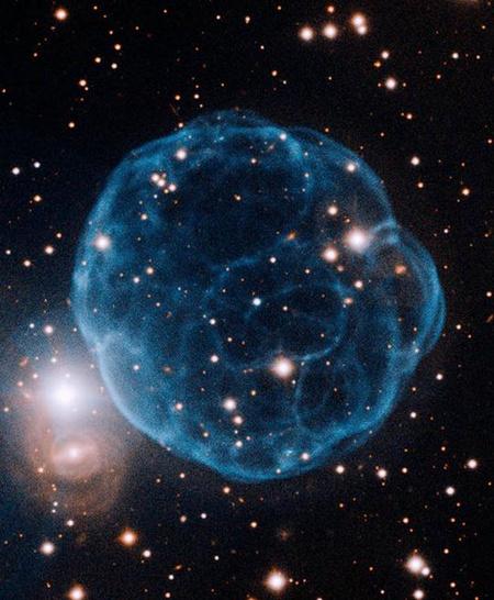 A Kronberger 61 (Kn 61) planetáris köd az északi Gemini teleszkóp felvételén. A köd kékes színű ragyogása elsődlegesen a kétszeresen ionizált oxigén emissziójának köszönhető. [Gemini Observatory/AURA, Travis Rector]