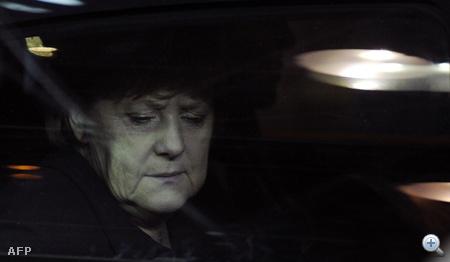 Angela Merkel arca az autó üvegén keresztül, amikor megérkezik egy informális munkavacsorára.