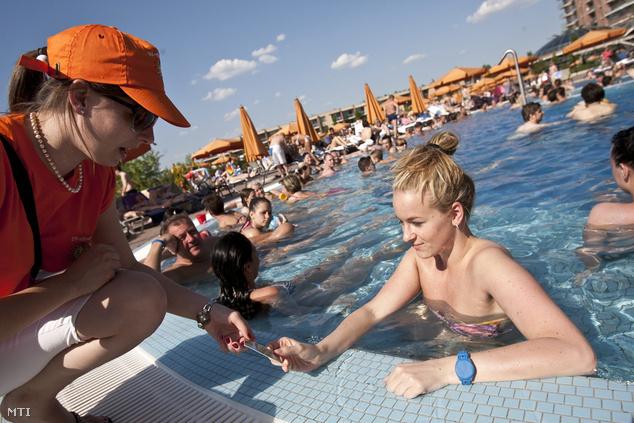 UV-fénymérőt ad egy látogatónak egy UV ellenőr a fővárosi Aquaworld strandján.