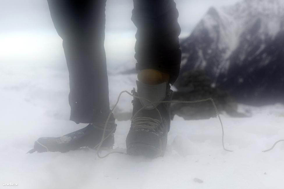 Erőss Zsolt a hajnali fagyban, az indulás előtt, a sátorból nézve. Zsolt speciális lábat használt a magashegyi mászáshoz.