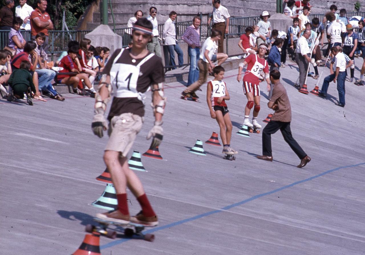 """Míg Kaliforniában a deszkázást azért találták ki, hogy az utcákon is """"szörfölhessenek"""", addig itthon - ahogyan Csehszlovákiában is - a síelés egyik kiegészítősportja volt. """"A hetvenes évek második felében a közalkalmazottak, az értelmiségiek körében a síelés nagyon népszerű volt, és a gördeszkázást a síelés élményének, például a szlalomozásnak a nyári gyakoroltatására használták. Ha jól emlékszem, én is így kaptam az első gördeszkámat""""- nosztalgiázott Petrányi Zsolt. A lapok szerint még a budapesti Orvosegyetem Sport Clubjának sí-szakosztályában is ezt használták a versenyzők felkészítésére. Nem is kellett sokat várni arra, hogy megrendezzék az első hivatalos megmérettetést. Az Ifjúsági Magazin és Magyar Televízió 1980-ban megrendezte az első deszkás versenyt a Millenáris Biciklipályán, ahol több egyszerű számban (szlalom, gyorsaság) indulhattak a versenyzők. A velodromot, amit most sorsára hagytak, azután kezdték el használni a fiatalok, miután az egyik fiút, aki egyébként idejárt bicikliedzésre, nyáron beengedte a gondnok."""