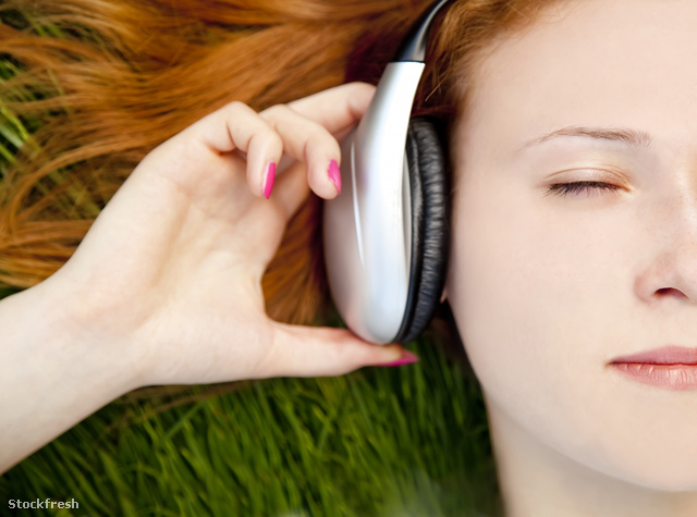 stockfresh 935386 redhead-girl-listening-music-at-green-grass si