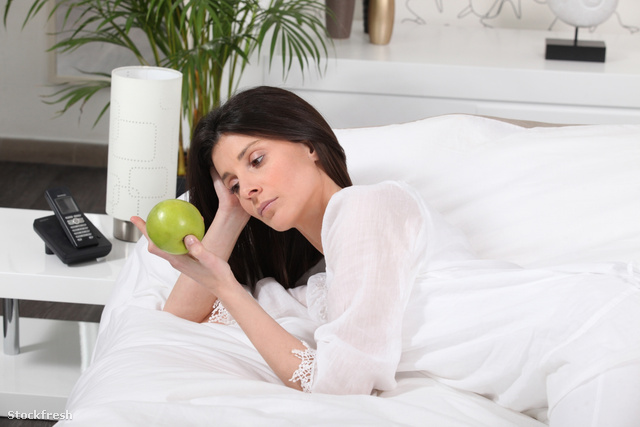 stockfresh 1688060 pensive-woman-on-bed-watching-an-apple sizeM