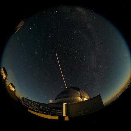 Halszemoptikás felvétel az Északi Gemini távcső mellől, amelyen lézeres műcsillag hasít magasan az égbe.