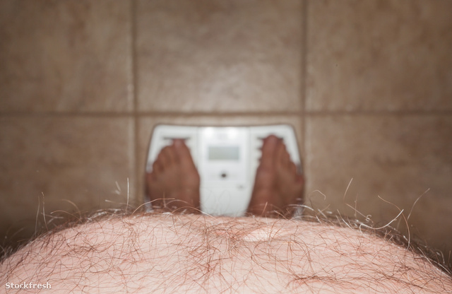 stockfresh 1673766 hairy-man-stomach-overhangs-feet-on-scales si